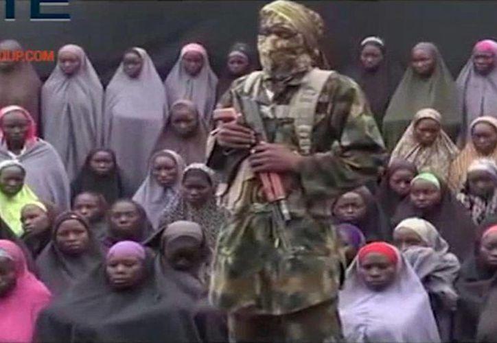 Imagen de un vídeo distribuido, este domingo 14 de agosto, en donde un presunto soldado de Boko Haram está delante de un grupo de chicas que supuestamente son algunas de las 276 alumnas secuestradas en abril de 2014. (Militant video/Site Institute via AP) AP no pudo verificar de forma independiente el contenido, fecha, lugar o autenticidad de este material.
