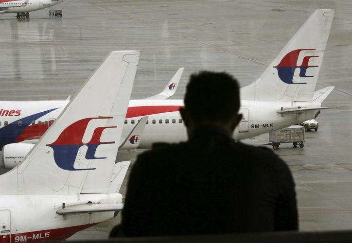 Una persona observa los aviones de Malaysia Airlines en la pista del Aeropuerto Internacional de Kuala Lumpur, Malasia. (Agencias)
