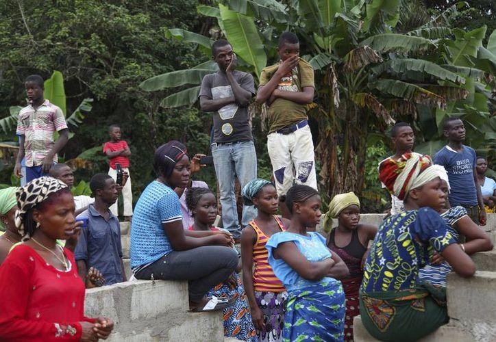 Varias personas asisten a un funeral de víctimas del ébola, a las afueras de Monrovia, Liberia. (Archivo/EFE)