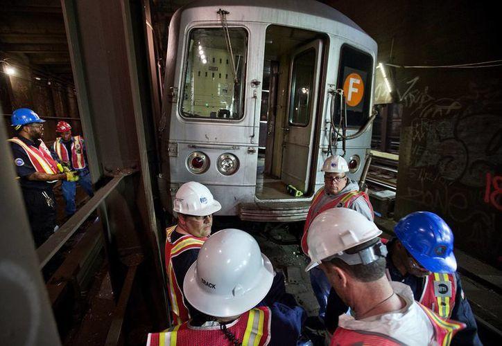 Foto proporcionada por la Autoridad Metropolitana de Transporte, en la que se observa a personal de la MTA que investigan la escena del descarrilamiento. (Agencias)