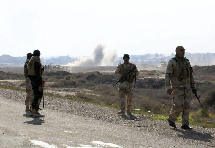 Soldados iraquíes y voluntarios de una milicia chií hacen guardia en una calle de Muadadiyah, en la provincia de Diyala, Irak, en una de las provincias iraquíes donde se concentran los combates contra el Estado Islámico. (Archivo/EFE)