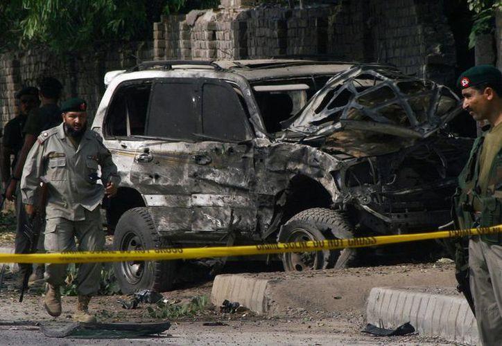 Funcionarios de seguridad paquistaníes y los equipos de rescate se reúnen en el sitio de la explosión de una bomba en Peshawar, Pakistán. (Agencias)