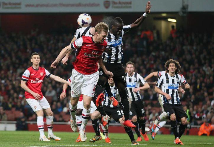 Per Mertesacker (c), del Arsenal, lucha por el esférico contra Cheick Tiote, del Newcastle. (Foto: AP)
