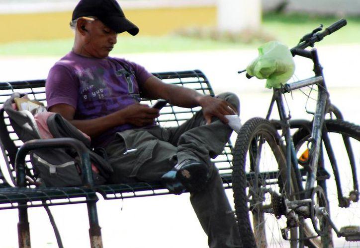 Más lugares públicos de Mérida tendrán conexión gratuita a Internet. En la imagen, un hombre sentado en la banca de un parque 'en línea', mientras se conecta a la red desde su celular. (Milenio Novedades)