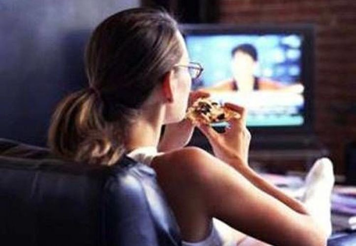 Comer mientras se ve televisión o se realiza otra actividad hace perder la noción de cuánto y qué se come. (Imagen: mejorconsalud.com)