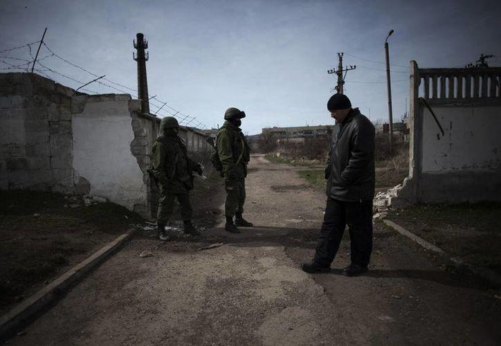 Un miembro de una unidad de pro rusa de autodefensa, derecho, se encuentra cerca de los soldados del Ejército ruso fuera de la base del Ejército de Ucrania en Perevalnoe, en el camino de Simferopol a Yalta, Ucrania. (Agencias)