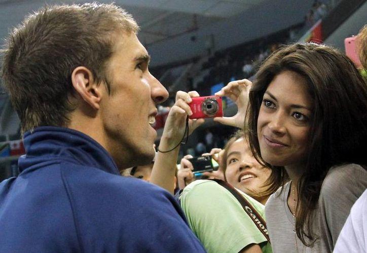 El ganador de 18 medallas olímpicas de oro, Michael Phelps, habla con su novia Nicole Johnson en el mundial de natación en Shanghai, China. (Archivo AP)