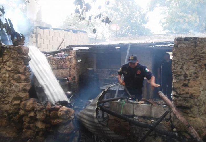 Un policía municipal revisa los escombros que quedaron tras un incendio en una vivienda en Motul. (SIPSE)