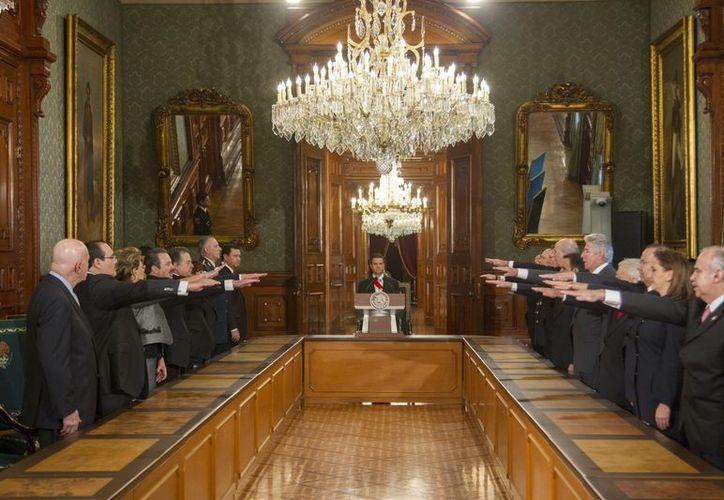 Peña Nieto (al centro y al fondo) al tomar protesta a los integrantes de su gabinete. (Presidencia)