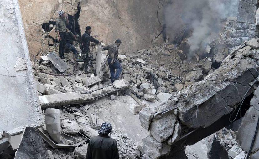 Imagen que muestra a unos civiles acudiendo a rescatar a posibles víctimas en el lugar donde se registró un ataque aéreo por parte del régimen sirio en el barrio de Kalase en Alepo, Siria. (Archivo/EFE)
