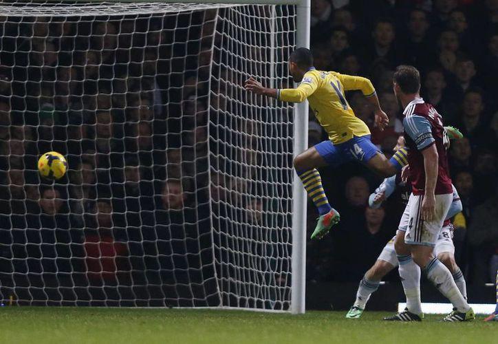 Theo Walcott (i), del Arsenal, celebra su segunda anotación frente al West Ham. (Agencias)