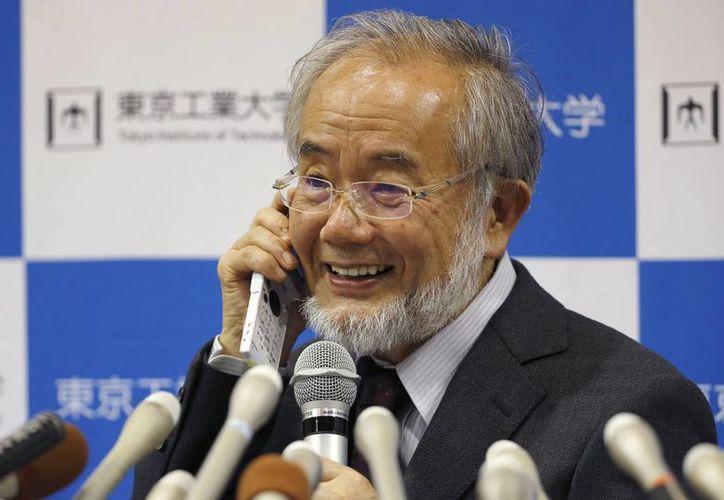 Yoshinori Oshumi sonríe mientras habla por teléfono con el primer ministro japonés, Shinzo Abe, durante una conferencia de prensa en el Instituto de Tecnología de Tokio. (AP/Shizuo Kambayashi)