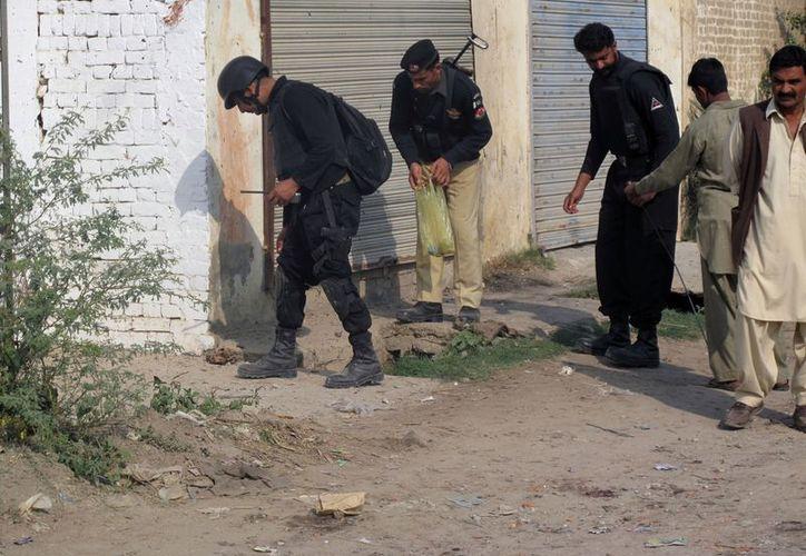 Policías de Pakistán  reunen pruebas en el sitio de la explosión de una bomba en Dera Ismail Khan. (Agencias)