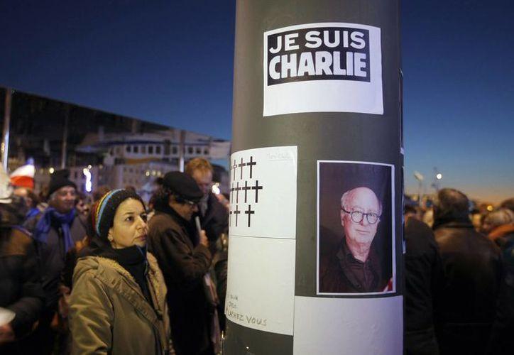 La gente mira la cruces dibujadas y el retrato del caricaturista francés Georges Wolinski que fue asesinado durante el tiroteo en la revista Charlie Hebdo de París, Francia. (Agencias)