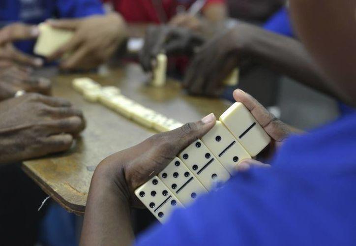 Estudiantes de vocacional aprenden estrategias del dominó en un salón de clases, en Kingston, Jamaica. (Agencias)