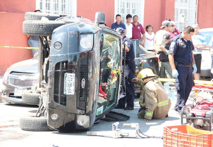 Bomberos y paramédicos tuvieron que trabajar más de una hora para poder sacar a una mujer de 61 años que se quedó atrapada, tras un accidente, dentro de su camioneta. (Aldo Pallota/SIPSE)