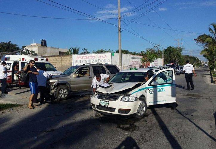 El taxista no respetó un alto e impactó a una camioneta, que golpeó a la mujer que caminaba en la banqueta. (Redacción/SIPSE)