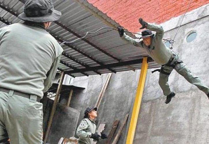 Tres guardias de la nueva fuerza de seguridad realiza prácticas de descenso a rapel. (Milenio)