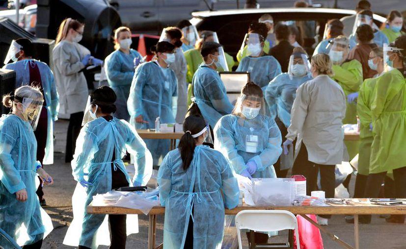 Personal médico se prepara para hacer pruebas de COVID-19 gratis a personas formadas en vehículos en Phoenix, Arizona. (Foto: AP).