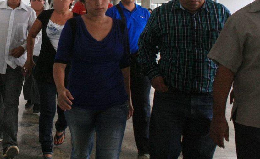 Imagen del momento en que Amílcar, asesino confeso de Erick, llega a la Fiscalía, acompañado de un grupo de personas entre familiares y funcionarios de la Codhey, para entregarse a las autoridades. (Jorge Sosa/SIPSE)