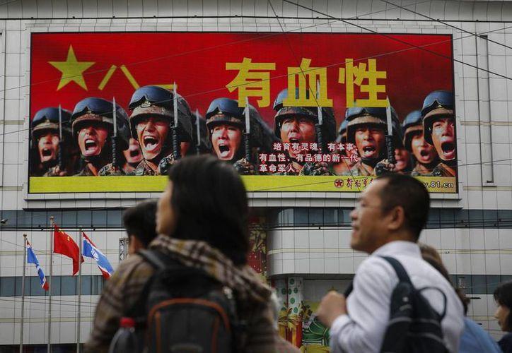 Cartel con imágenes de soldados que busca reclutar gente para el Ejército de Liberación Popular chino. (Agencias)