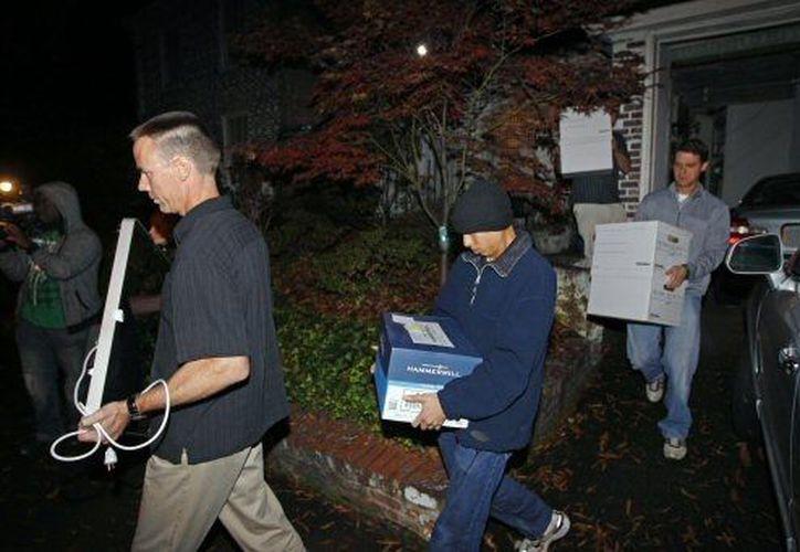 Agentes de la FBI transportan materiales encontrados en casa de Paula Broadwell. (Agencias)