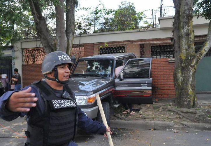 Autoridades efectúan el levantamiento de los cuerpos del expresidente de la Corte Centroamericana de Justicia, José Eduardo Gauggel, y de su hijo, hoy 10 de abril de 2015, en San Pedro Sula, Honduras. (EFE)