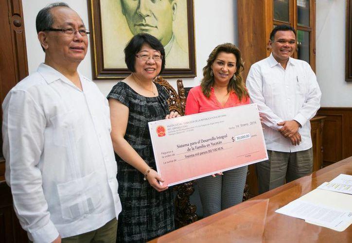 El embajador de China en México, Qiu Xiaoqi, con su esposa Liu Min,, al momento de hacer entrega de un apoyo económico al DIF Yucatán. El gobernador Rolando Zapata y su esposa, Sara Blancarte, titular del DIF estatal, lo reciben.