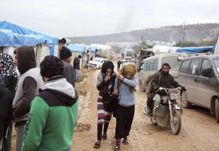 Sirios, evacuados de Alepo, caminan en un campo de refugiados cerca de Idlib, Siria. (AP)