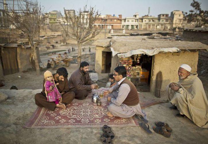 Una familia de refugiados afganos toman el té y charlan mientras están sentados en frente de su casa de barro en las afueras de Islamabad, Pakistán. (Agencias)