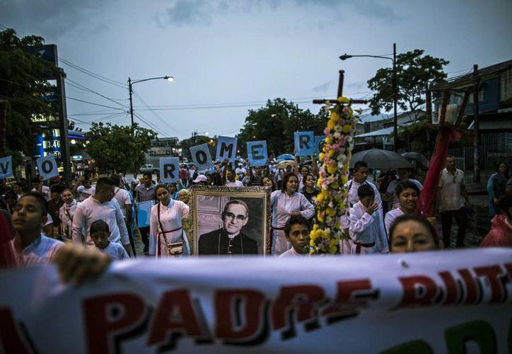 Las personas marchan con una imagen del arzobispo católico Oscar Arnulfo Romero, durante la vigilia de la ceremonia de su beatificación, en San Salvador, El Salvador. (Agencias)