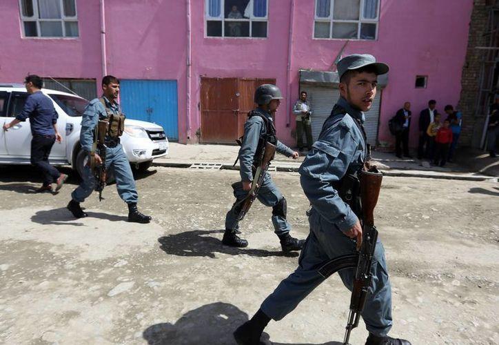 Fuerzas de seguridad afganas inspeccionan el lugar donde ocurrió un ataque suicida en Kabul. Milicianos talibanes que libran una guerra contra el gobierno afgano desde hace más de una década expresaron la disposición de suavizar sus posiciones. (Foto AP/Rahmat Gul)