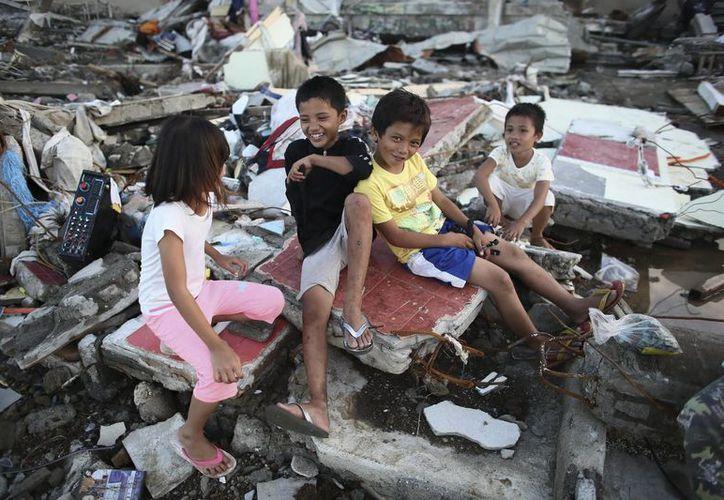 Un grupo de niños posa en la devastada ciudad de Tacloban tras el paso del Tifón Haiyan, en la isla de Leyte, Filipinas. (EFE)