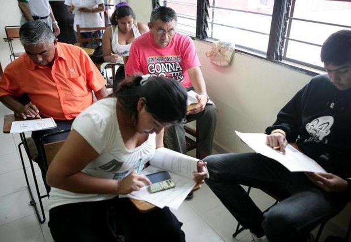 En la actualidad Yucatán ocupa el sitio número 13 a nivel nacional respecto al analfabetismo, lo que afecta al 4.6 por ciento de la población. En la imagen, varios adultos presentan un examen en una escuela. (Milenio Novedades)