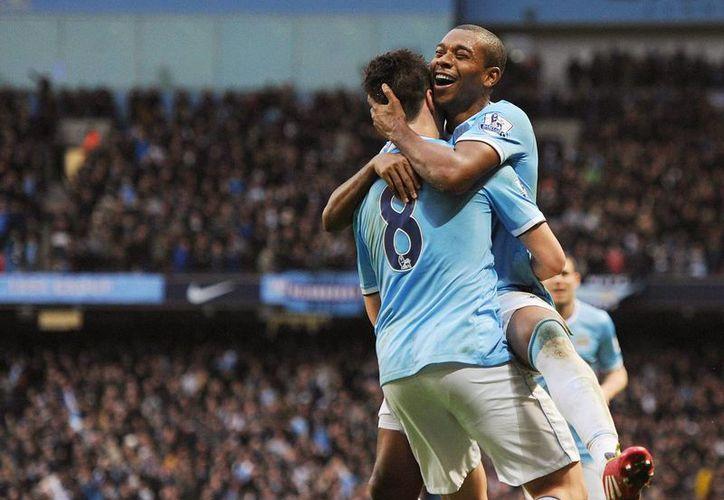 Fernandinho (d), del Manchester City, celebra con su compañero Samir Nasri uno de los goles de su equipo durante el partido de la Premier League que han jugado Manchester City FC y Arsenal FC. (EFE)