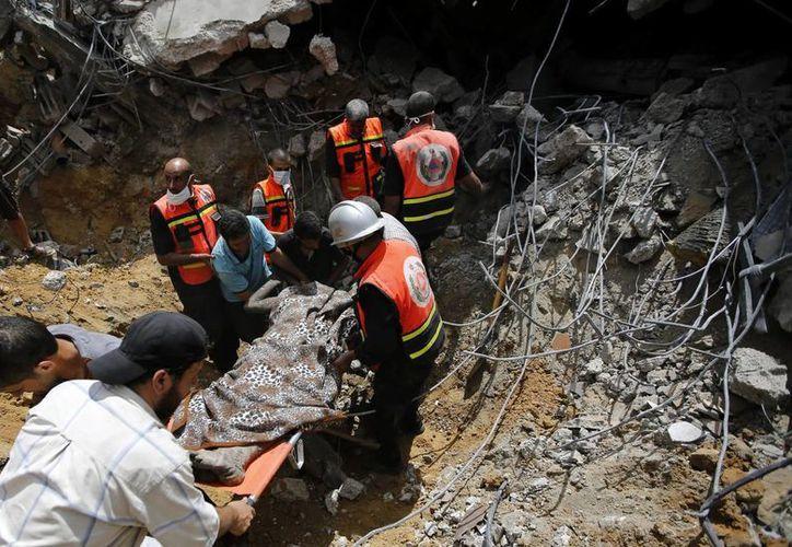 Médicos palestinos recuperan un cadáver entre los escombros de una casa tras un ataque aéreo de Israel al este de la ciudad de Khanyounis, al sur de la Franja de Gaza. (EFE)