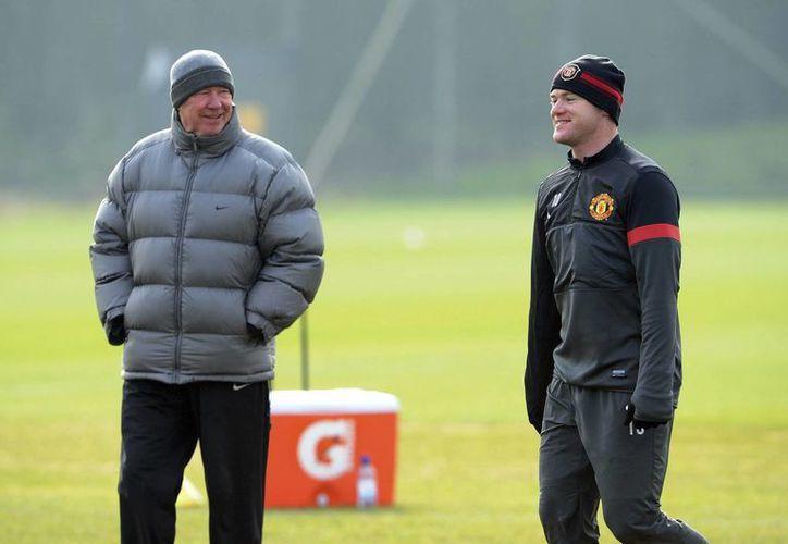 Ferguson (izq) conversa con Wayne Rooney durante un entrenamiento en Carrington. (EFE)