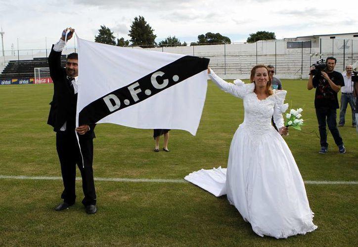 Elena Vargas (d) y su esposo Marcelo Gómez desplegaron una bandera del club Danubio tras su boda celebrada en el estadio Jardines del Hipódromo, en Montevideo, Uruguay. (EFE)