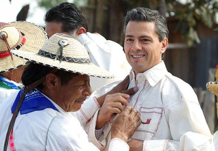 Un indígena de Durango obsequia al Presidente una camisa bordada durante la inauguración de la carretera Mezquital-Huazamota, en diciembre pasado. (Archivo/Presidencia)