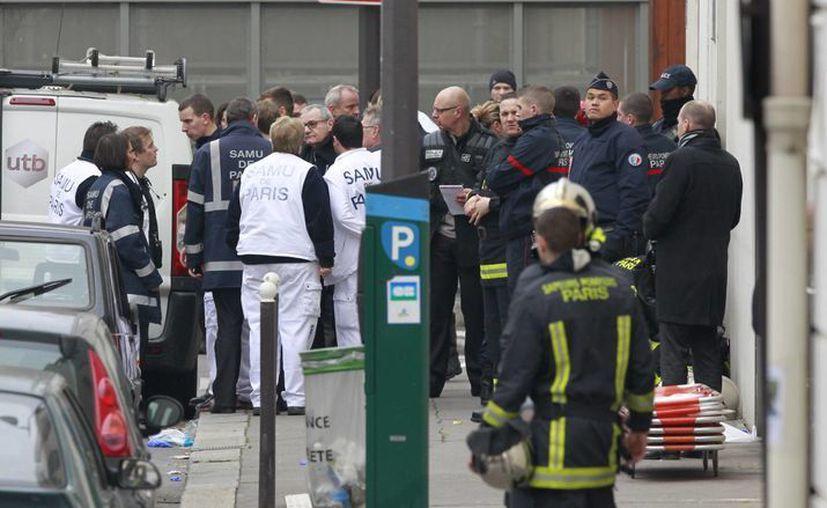 Los agentes de policía y trabajadores de rescate se reúnen en la escena después de que hombres armados irrumpieron en un periódico francés, en París. (Agencias)