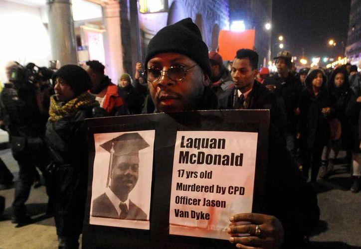 Un manifestante alza un cartel durante una marcha por Laquan McDonald, de 17 años, muerto de 16 balazos por un agente de policía de Chicago. McDonald, cuyo nombre corean los manifestantes marcharon hacia la zona comercial más lujosa de la ciudad. (AP Foto/Paul Beaty)