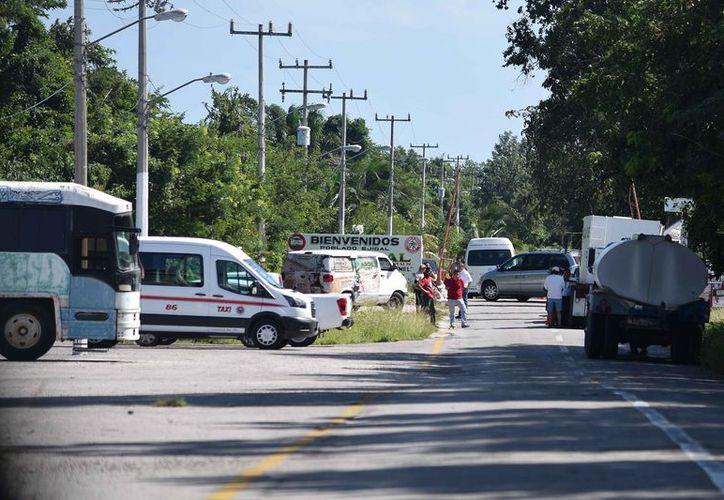 Colocaron vehículos para evitar el paso hacia el poblado. (Gustavo Villegas/SIPSE)