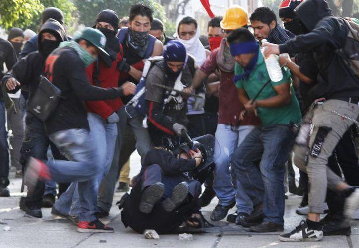 Los manifestantes agredieron a palos a los policías. (Agencias)