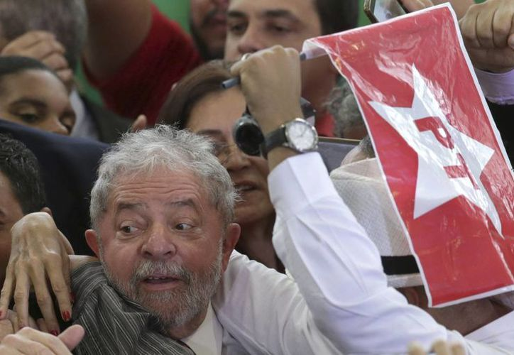 Partidarios abrazan al expresidente brasileño Luiz Inácio Lula da Silva tras su juramentación como jefe de gabinete en el palacio de Planalto, Brasilia. (Agencias)