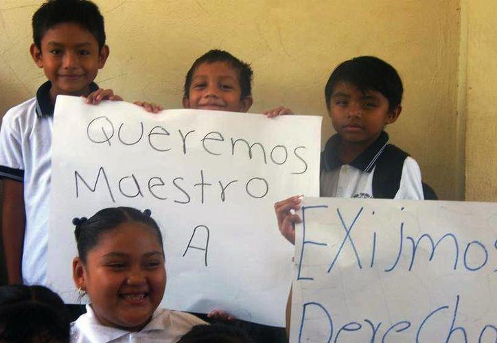Los estudiantes, acompañados de sus padres, sostuvieron carteles en los que exigían la asignación de un maestro. (Juan Cano/SIPSE)