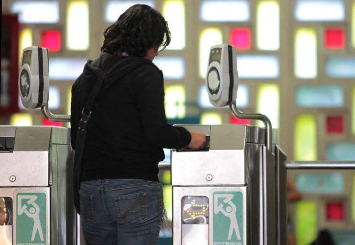Con la publicación, en la Gaceta Oficial, quedó establecida la nueva tarifa del Metro, en el DF: a partir del próximo viernes el precio del viaje será de 5 pesos. En la imagen, una mujer introduce su boleto en una estación del sistema colectivo de transporte. (Archivo/NTX)