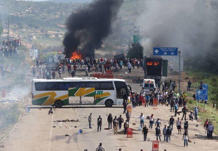 Maestros inconformes que bloqueaban una carretera federal se refugian detrás de un autobús de pasajeros y otros camiones en llamas mientras se enfrentan con policías antimotines. (Agencias)