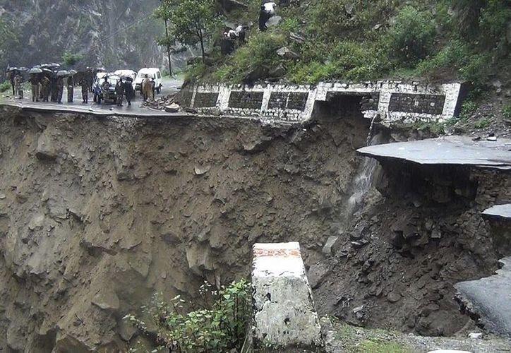 Varias personas observan una carretera destrozada por las lluvias torrenciales en Badrinath, Estado de Uttarakhand, India. (EFE)
