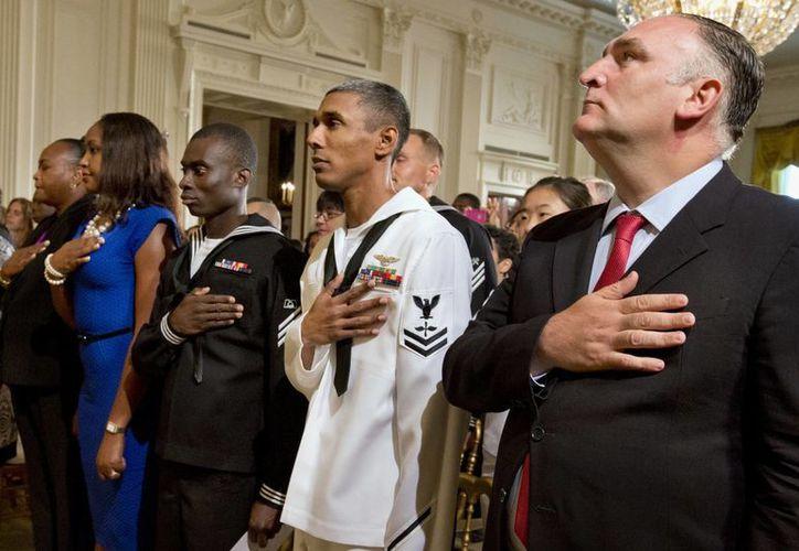 Asistentes a la ceremonia de naturalización para los miembros en servicio activo y civiles escuchan a la Banda de la Marina tocar el himno de EU. (Agencias)
