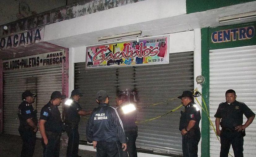 Agentes municipales aguardan la llegada de los ministeriales en la tienda Garabatos del centro de Mérida. (Milenio Novedades)